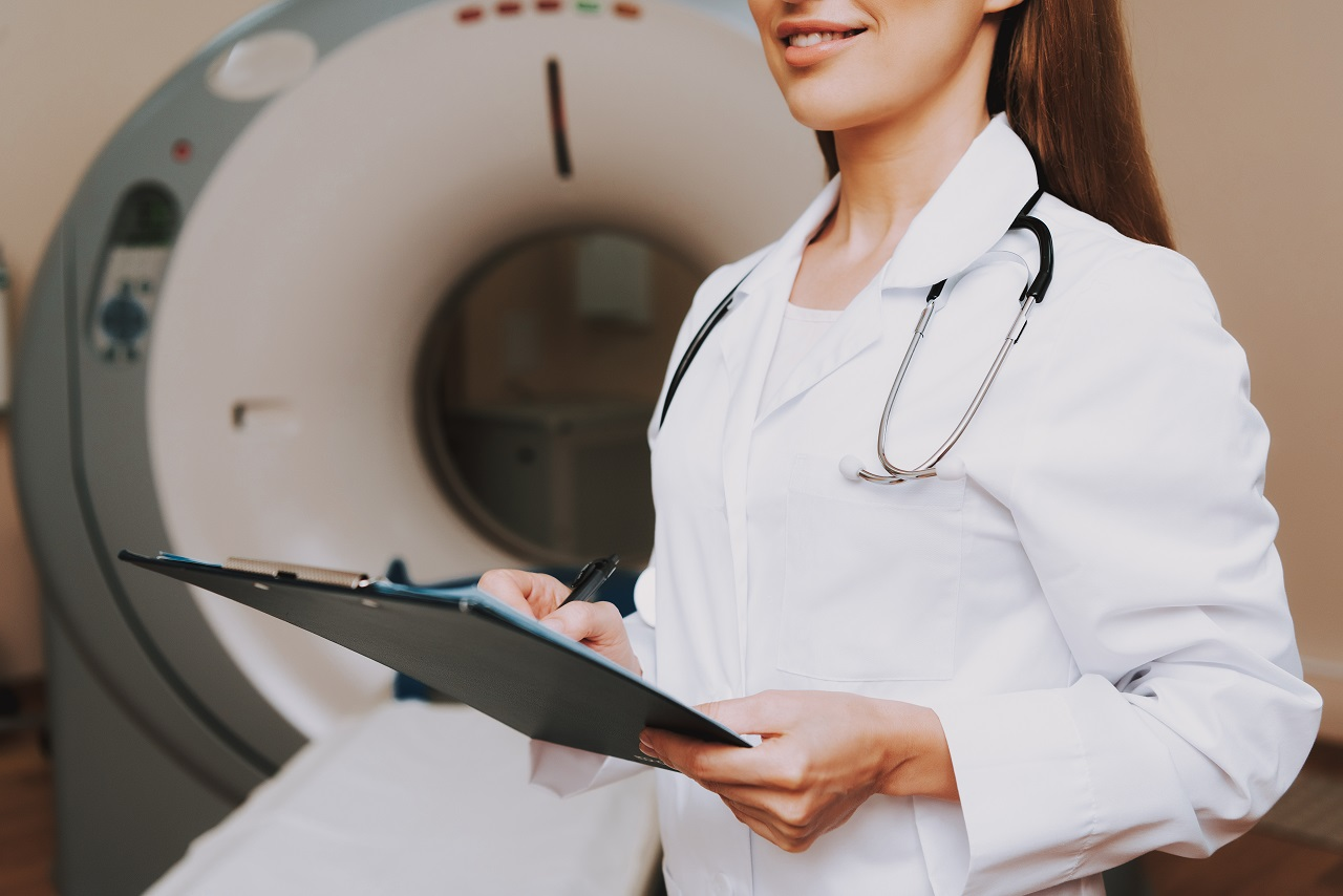 Close up of a female doctor holding a clipboard in front of an MRI machine