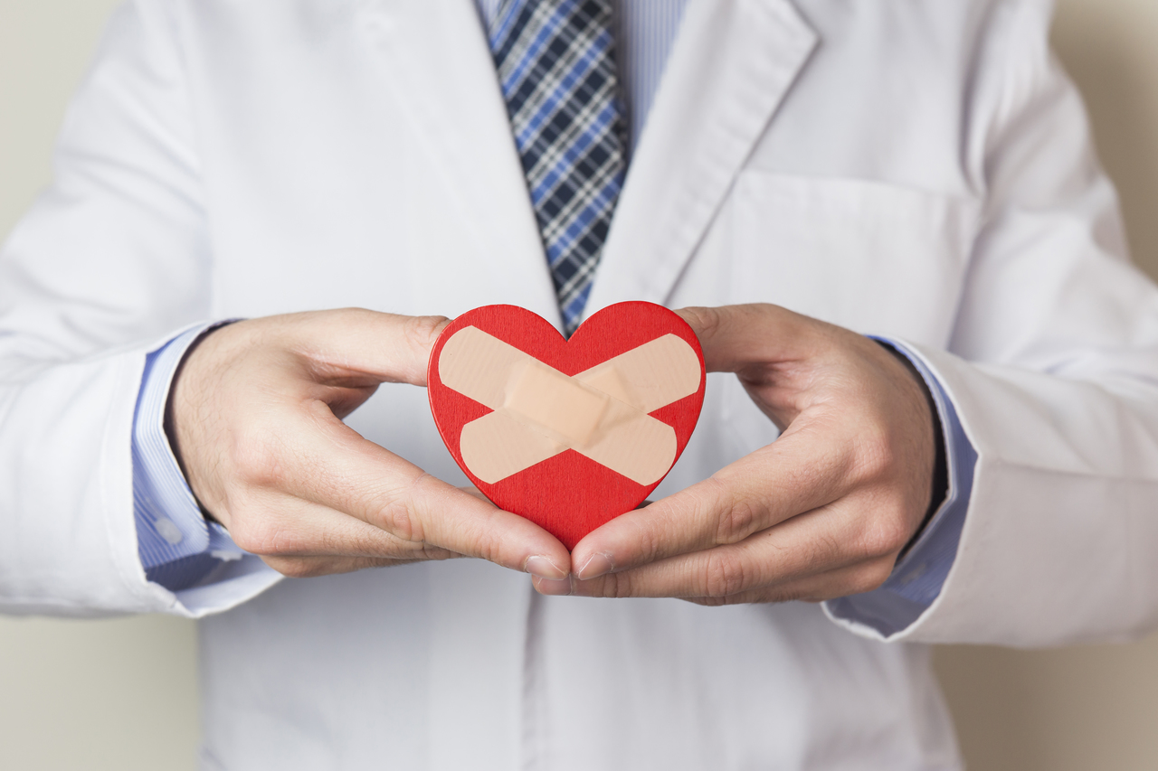 A doctor holding a heart with band aids