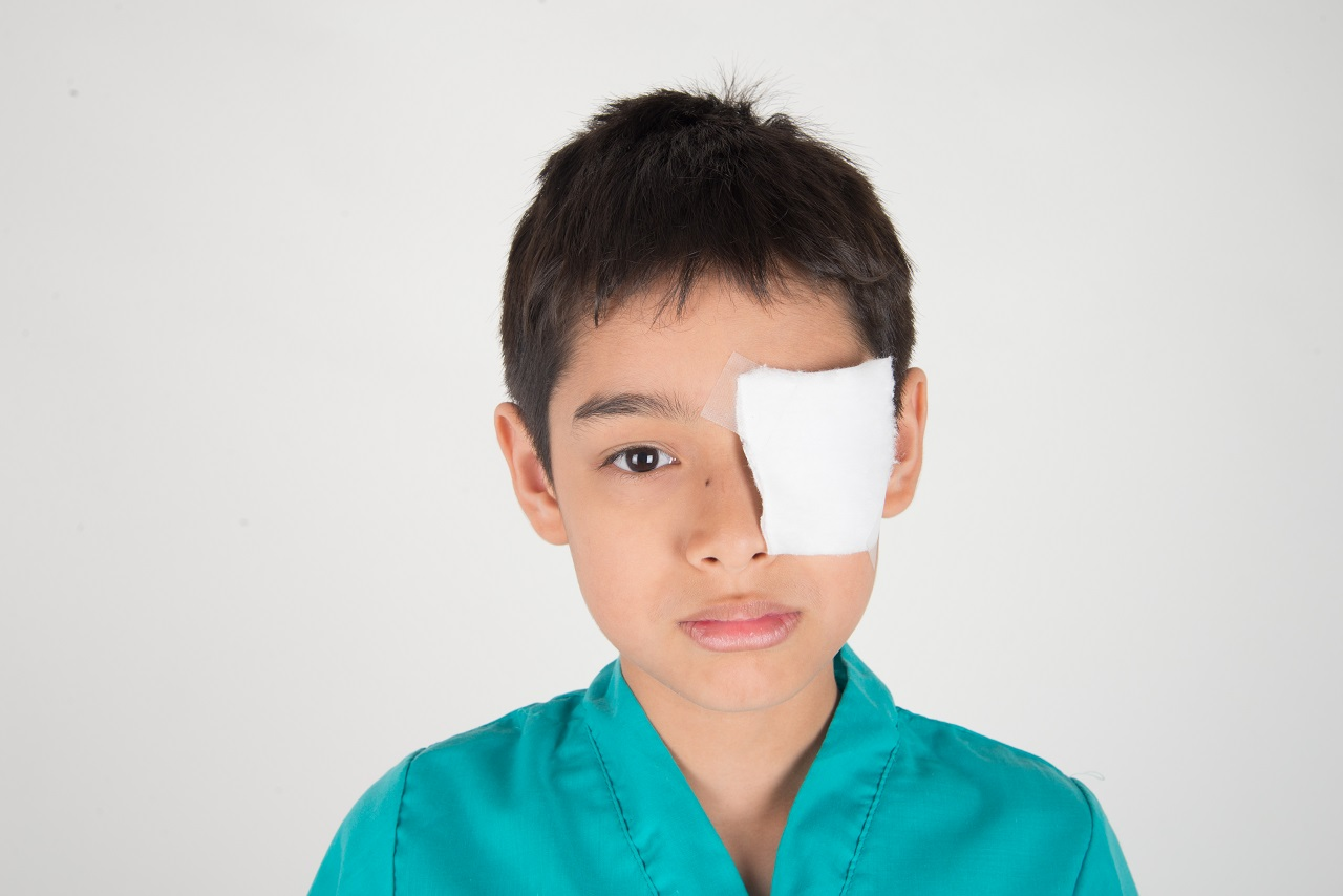 A young boy with an eye patch bandage