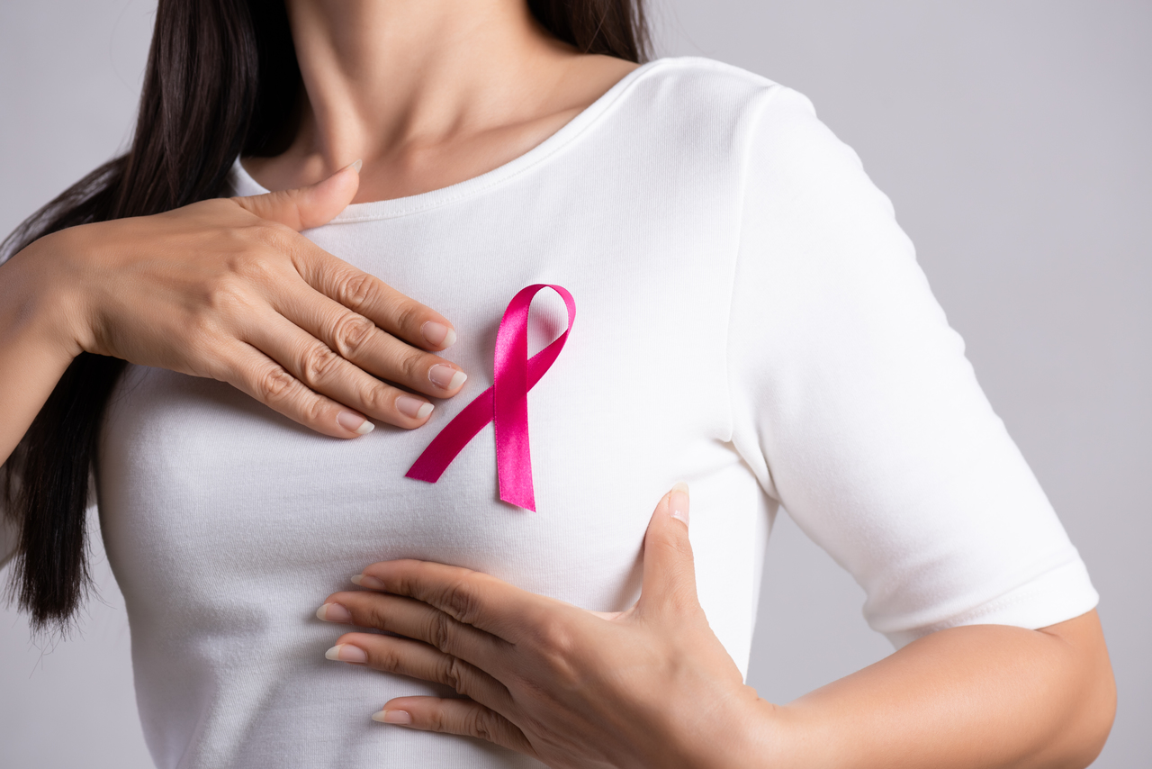 A woman in a white shirt with a pink ribbon on her breast area