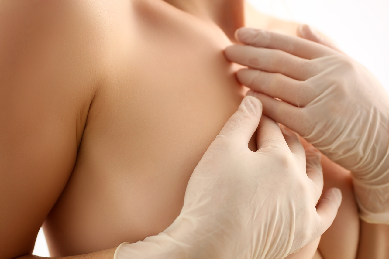 A naked woman examining her breasts for cancerous lumps
