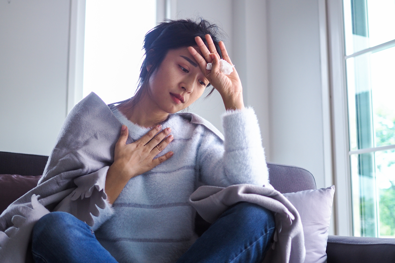 A woman feeling COVID-19 symptoms at home