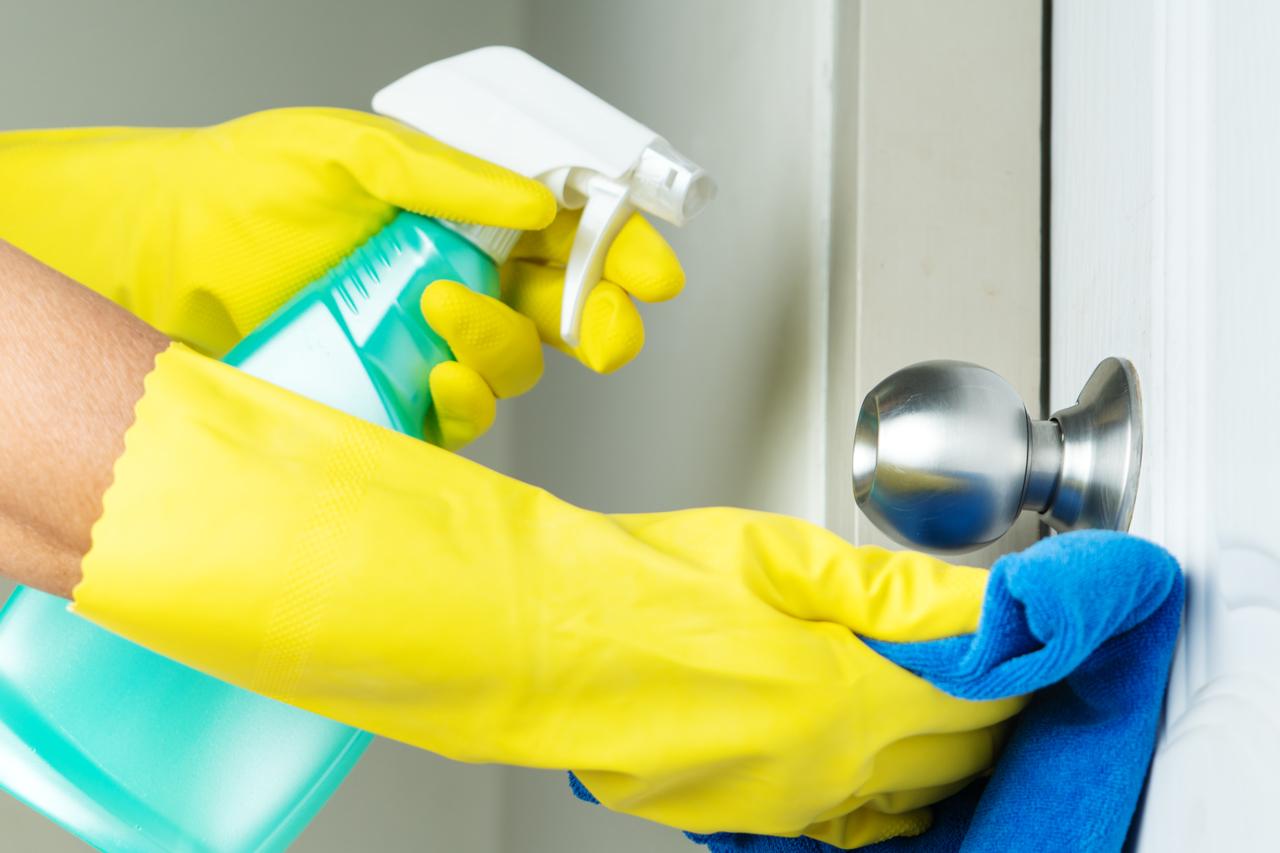 A person disinfecting a doorknob