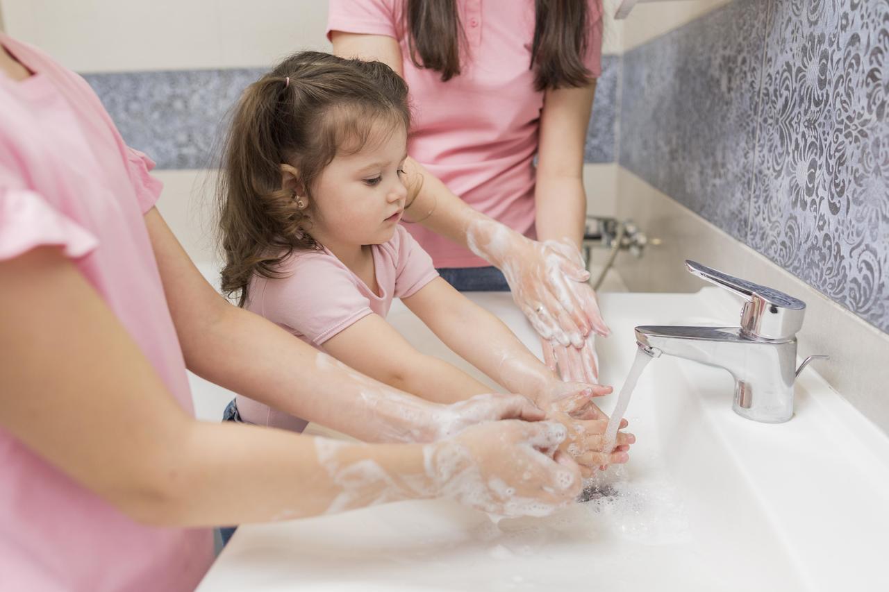 A little girl washing her hands
