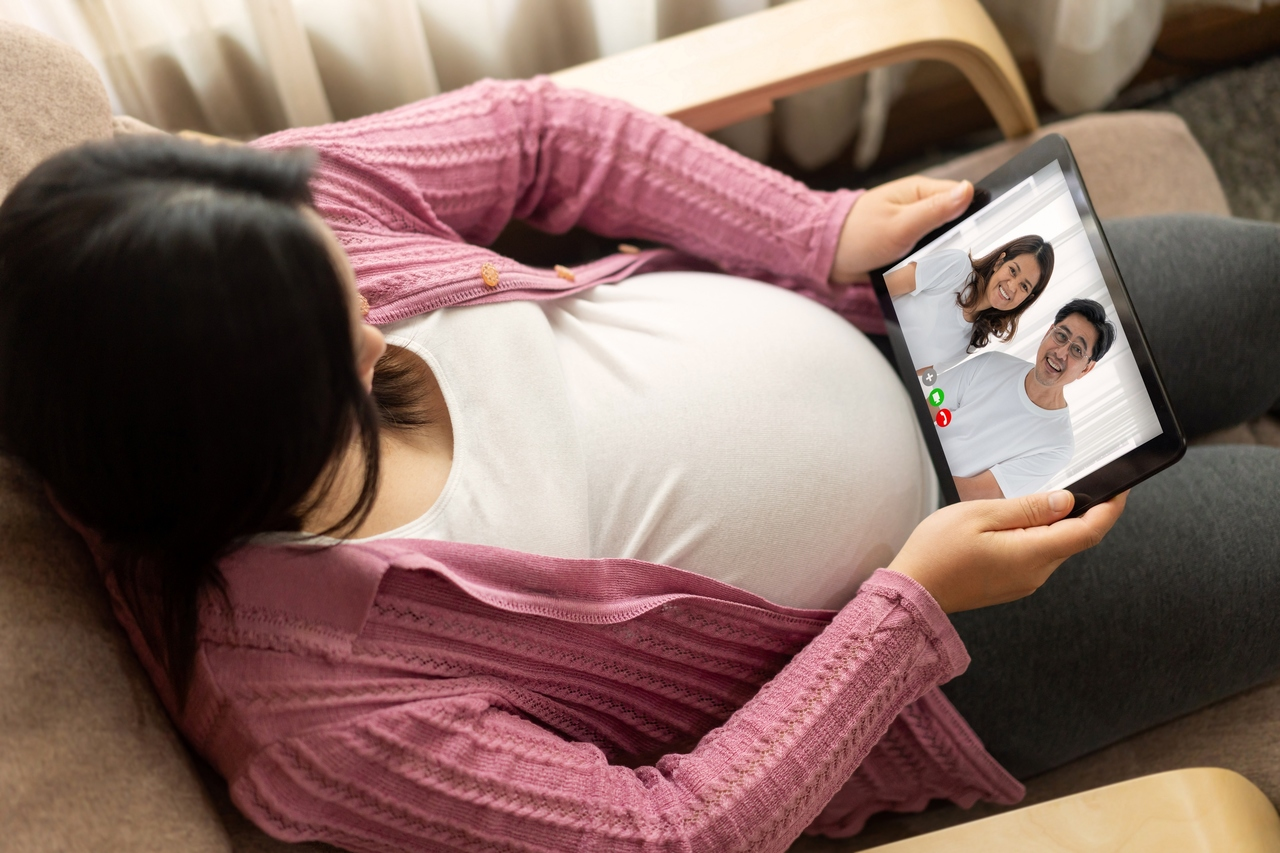 A pregnant woman on a video call at home