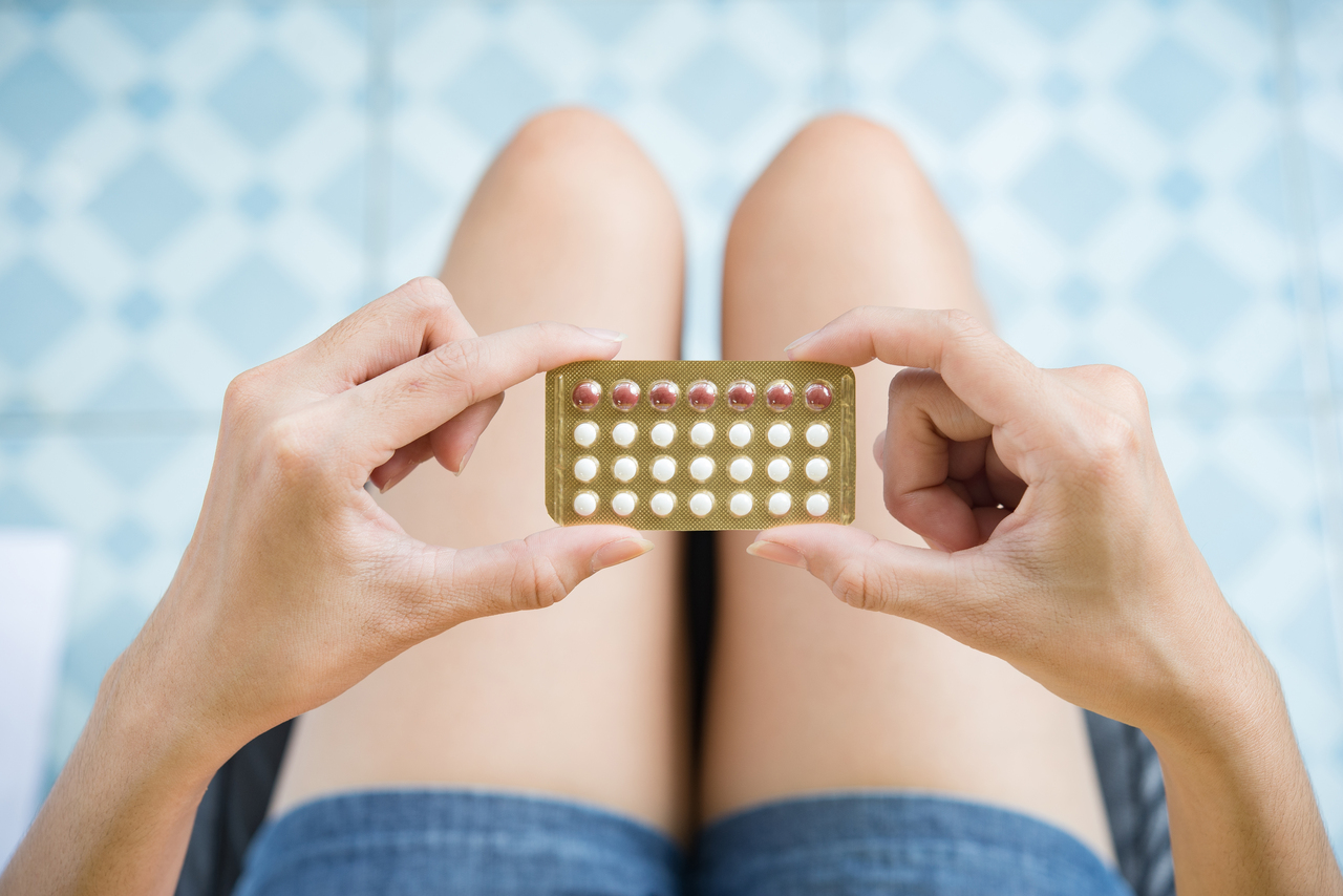A woman holding birth control pills for PCOS