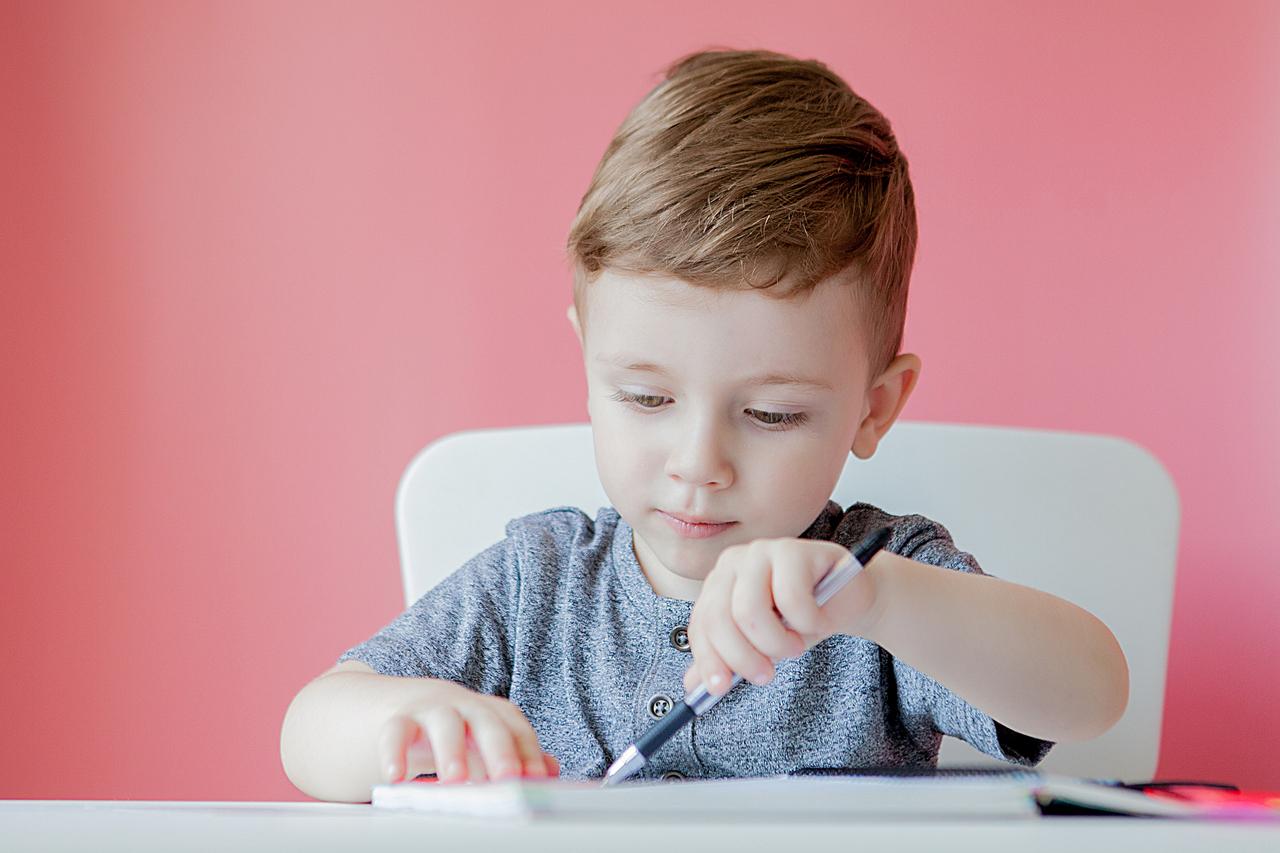 A little boy having trouble holding a pen