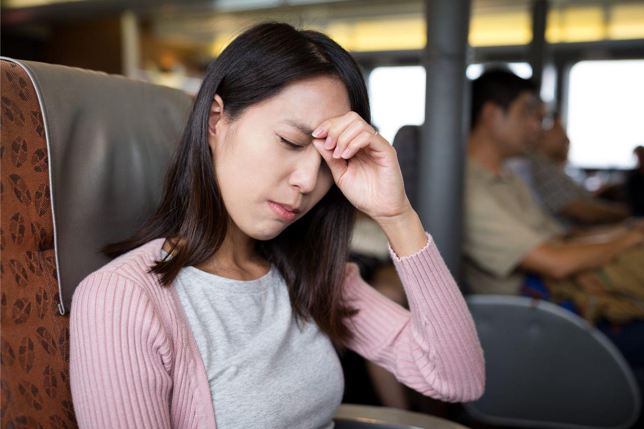 Woman experiencing a headache inside a bus