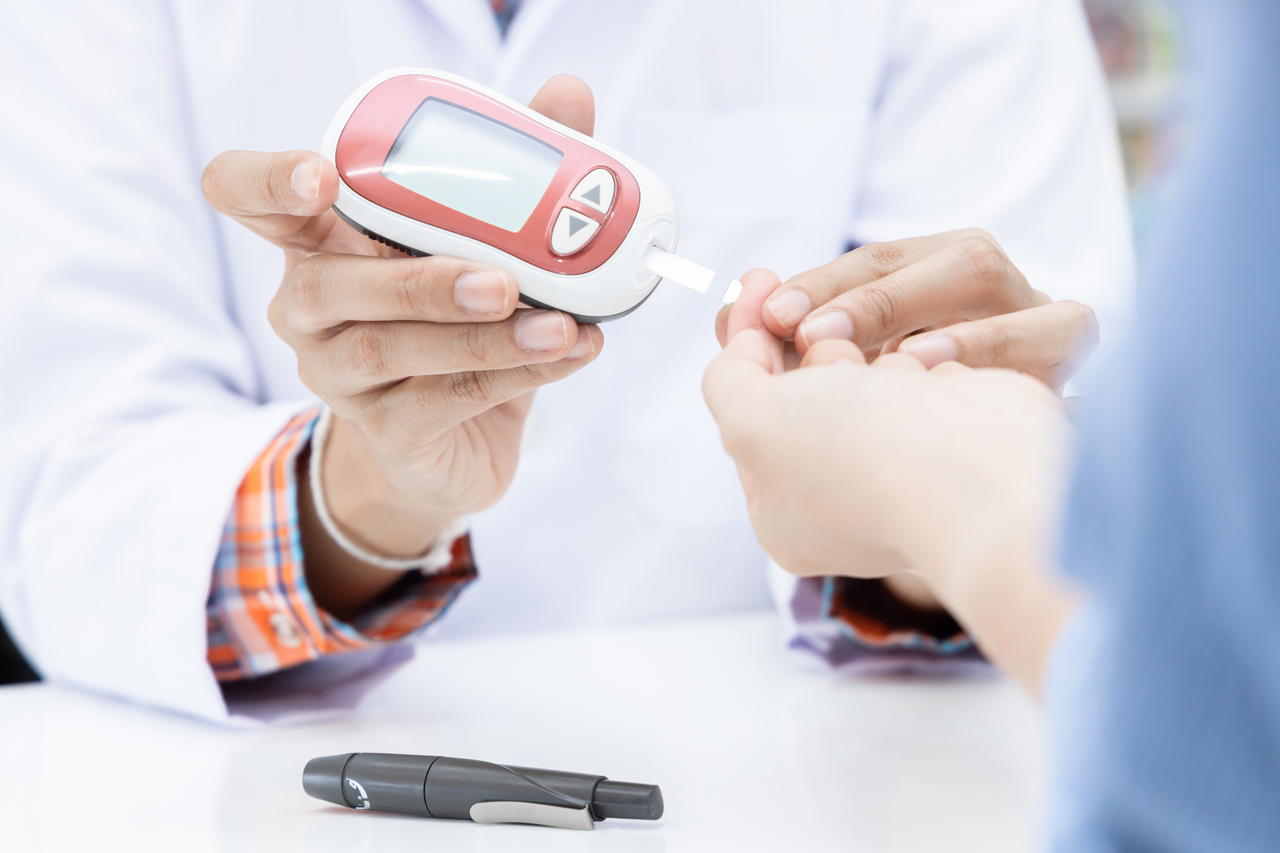 Doctor checking blood glucose level for insulin determination in patient